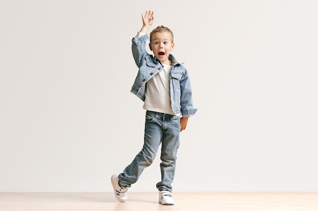 Le portrait de mignon petit garçon enfant dans des vêtements de jeans élégants regardant la caméra contre le mur blanc du studio. concept de mode pour enfants