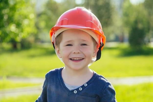 Portrait de mignon petit garçon européen dans un casque de construction dans le parc sur fond d'herbe verte et d'arbres. concept d'orientation professionnelle