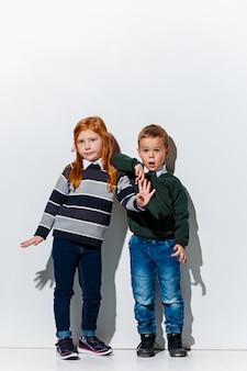 Le portrait de mignon petit garçon et fille en vêtements jeans élégants posant