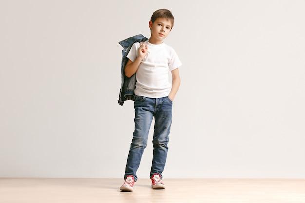 Le portrait de mignon petit garçon en jeans élégants regardant la caméra au studio