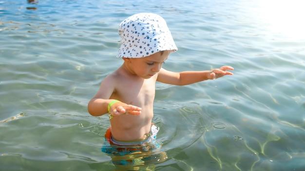 Portrait de mignon petit garçon marchant dans la mer.