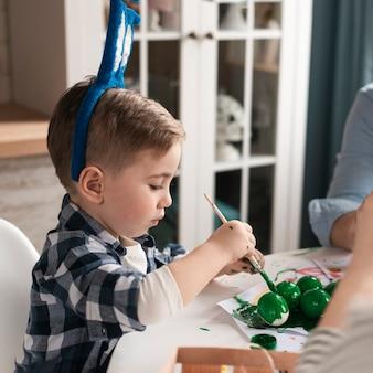 Portrait de mignon petit garçon peignant des oeufs pour pâques