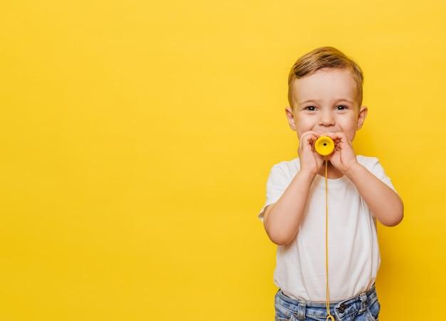 Portrait d'un mignon petit garçon riant sur fond jaune