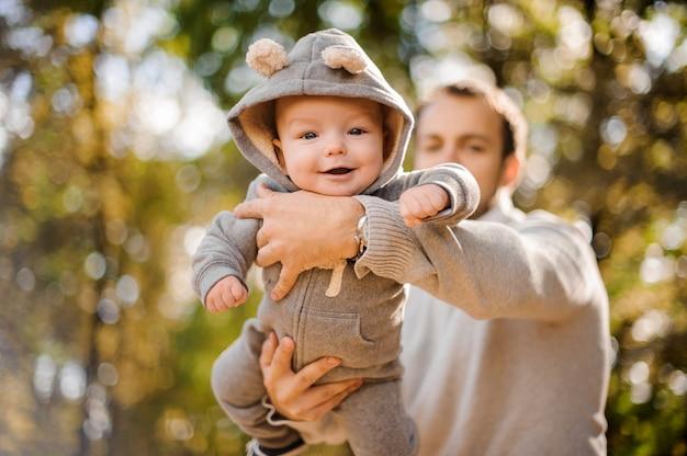 Portrait d'un mignon petit garçon souriant dans les mains du père
