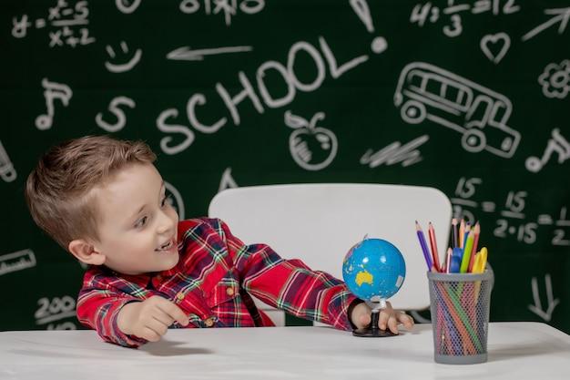 Portrait de mignon petit garçon tenant en mains petit globe sur fond de tableau noir. prêt pour l'école. retour à l'école.