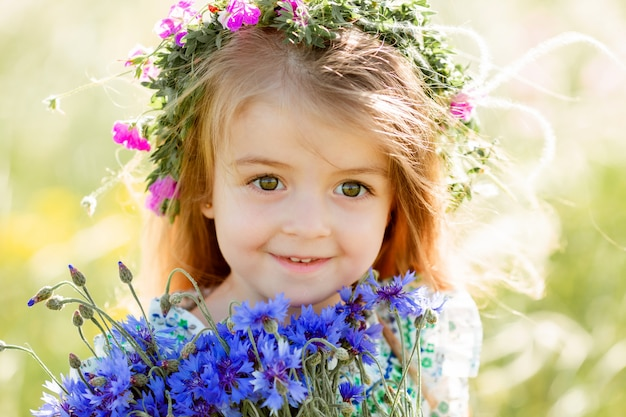 Portrait d'une mignonne petite fille avec une couronne sur la tête en souriant tenant des fleurs sauvages de bleuet