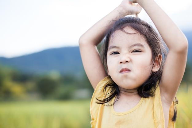 Portrait de mignonne petite fille enfant asiatique, visage drôle et en colère.