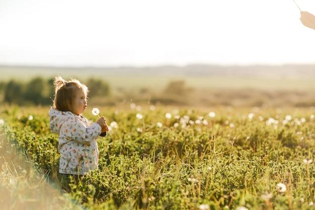 Portrait d'une mignonne petite fille en journée d'été ensoleillée à fond de nature verte
