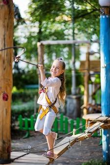 Portrait d'une mignonne petite fille qui marche sur un pont de corde dans une corde de parc d'aventure.