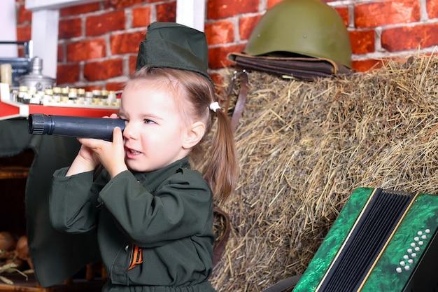 Portrait d'une mignonne petite fille en uniforme sur un fond rustique. jour de la victoire, jour férié le 9 mai.
