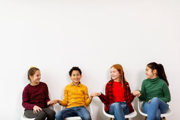 Portrait de mignons petits enfants en jeans assis sur des chaises sur un mur blanc