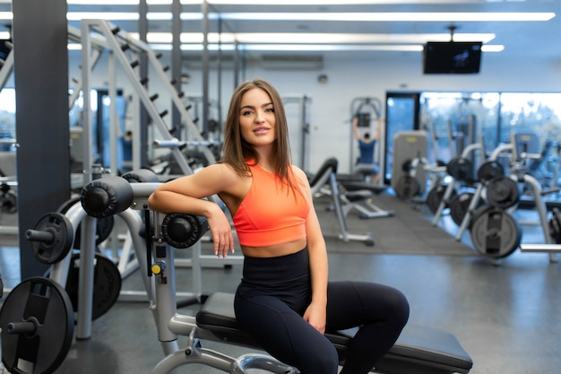 Portrait de mince belle jeune femme se détendre dans une salle de sport après un entraînement intensif