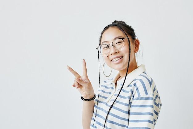 Portrait minimal d'une adolescente asiatique posant et regardant la caméra sur fond blanc, espace pour copie