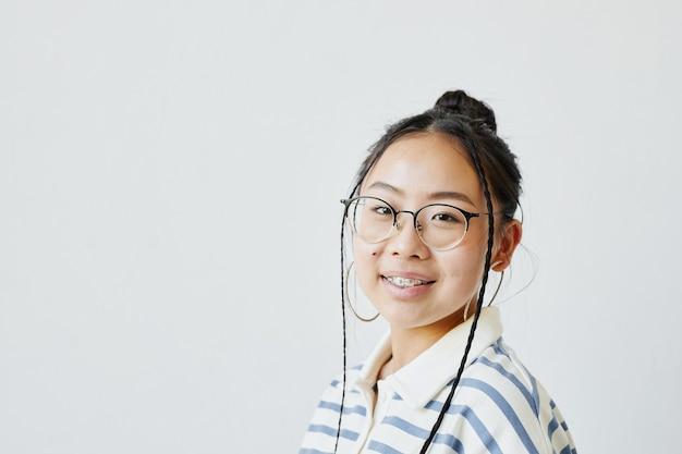 Portrait minimal d'une adolescente asiatique regardant la caméra sur fond blanc, espace pour copie