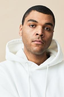 Portrait minimal d'un bel homme métis portant un sweat à capuche blanc et regardant la caméra tout en posant sur fond clair