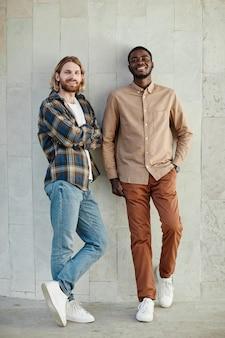 Portrait minimal de deux jeunes hommes posant et souriant à la caméra en se tenant debout contre le mur en milieu urbain
