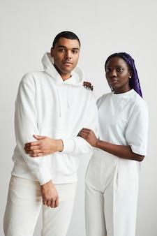 Portrait minimal d'un jeune couple de race mixte vêtu de blanc tout en posant pour la caméra
