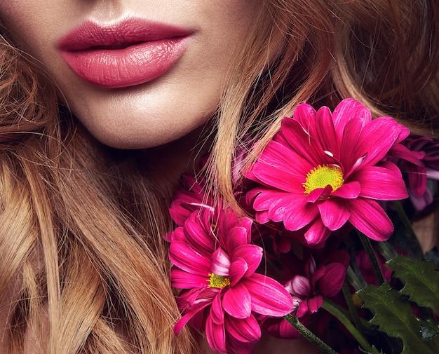 Portrait de mode de beauté du jeune mannequin femme blonde avec un maquillage naturel et une peau parfaite avec une fleur de chrysanthème сrimson brillant posant