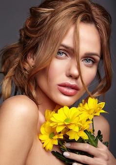 Portrait de mode de beauté du modèle jeune femme blonde avec un maquillage naturel et une peau parfaite avec une fleur de chrysanthème jaune vif posant