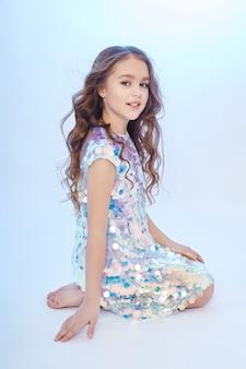 Portrait de mode beauté d'une jeune fille vêtue d'une robe sur fond clair