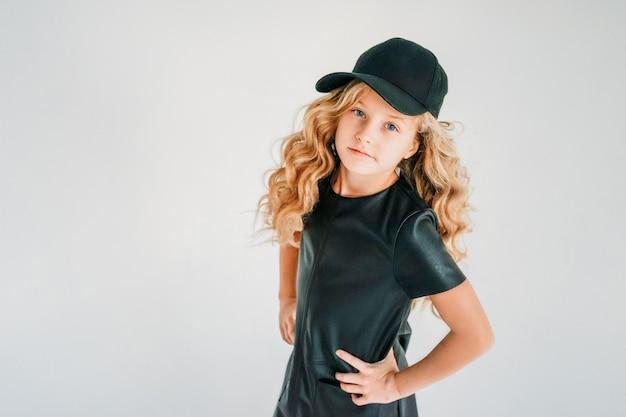 Portrait de mode beauté de sourire fille bouclée de cheveux bouclés en robe en cuir noir et casquette de baseball sur blanc isolé