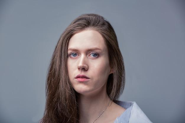 Portrait à la mode de la belle jeune femme aux yeux bleus sur fond gris