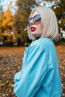 Portrait de mode d'une belle jeune femme blonde avec des lunettes de soleil élégantes dans un manteau bleu à la mode sur la nature sur fond de feuillage d'automne jaune