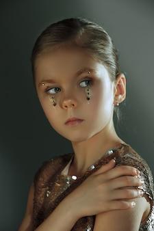 Le portrait de mode de la belle jeune fille préadolescente au studio