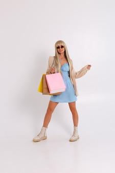 Portrait à la mode d'une blonde élancée aux cheveux longs dans une robe bleu clair et une chemise en velours côtelé