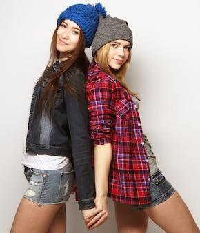 Portrait de mode de deux meilleures amies élégantes et sexy de filles hipster, vêtues de jolies tenues et chapeaux de butin. sur fond gris.