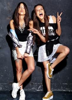 Portrait de mode de deux modèles brune souriante dans des vêtements de hipster décontracté noir d'été posant près d'un mur gris foncé. montrant le signe de la paix