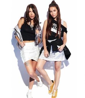Portrait de mode de deux modèles brune souriante dans des vêtements de hipster décontractés d'été isolés sur blanc. toute la longueur