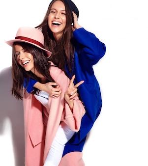 Portrait de mode de deux modèles de femmes brune souriante en pardessus hipster décontracté d'été isolé sur blanc. filles se tenant sur le dos
