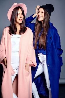 Portrait de mode de deux modèles de femmes brune souriante en pardessus hipster décontracté d'été posant sur gris. toute la longueur