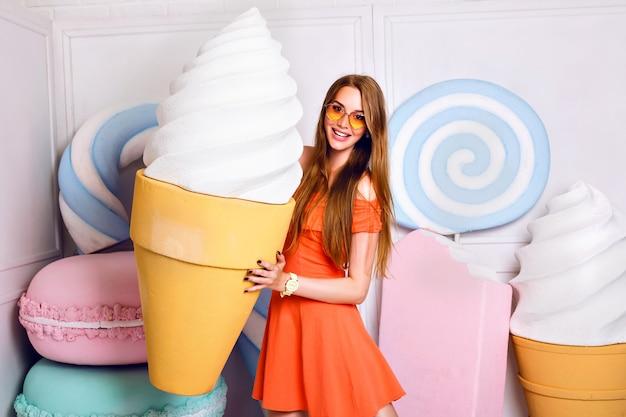 Portrait de mode drôle de jolie femme blonde tenant une glace géante, posant près de grande fausse douceur, couleurs pastel, belle robe, magasin de bonbons.