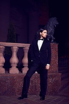 Portrait de mode élégant jeune homme aux cheveux longs. modèle masculin attrayant et beau en costume noir avec moustache dans la rue la nuit
