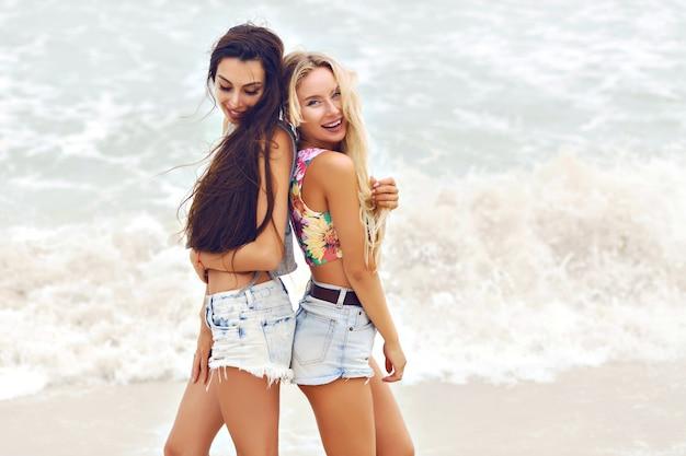 Portrait de mode d'été en plein air de deux jolies meilleures filles fiends, posant près de l'océan, temps nuageux venteux.