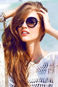 Portrait de mode d'été en plein air de femme sexy en tenue élégante de poussin boho et lunettes de soleil posant sur la plage tropicale, vue imprenable sur l'océan bleu clair