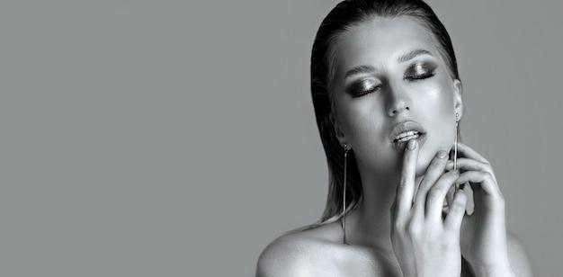 Portrait de mode d'une femme blonde sensuelle aux cheveux mouillés et à la peau parfaite. modèle posant les épaules nues sur fond gris. espace libre