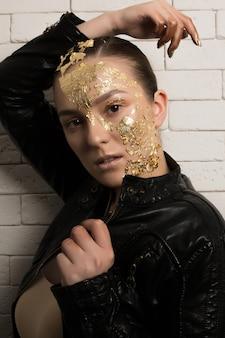 Portrait de mode d'une femme brune élégante avec une feuille d'or sur le visage et le cou, portant une veste en cuir