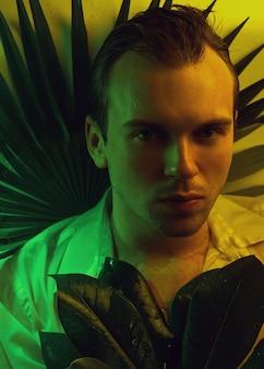 Portrait de mode gros plan d'un bel homme mal rasé caucasien sous l'eau en chemise blanche mouillée sexy regardant le visage fort de la caméra, fond de plantes