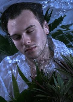 Portrait de mode gros plan d'un bel homme mal rasé caucasien sous l'eau en chemise blanche mouillée sexy yeux fermés visage fort, fond de plantes