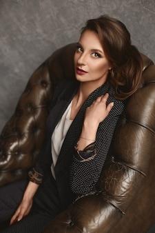 Portrait de mode en gros plan d'une jeune femme avec un maquillage et une coiffure parfaits dans un costume et un chemisier à la mode posant dans un fauteuil en cuir vintage de luxe