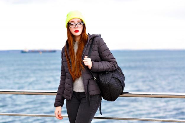Portrait de mode hipster en plein air de jeune jolie femme aux longs poils roux, posant près du bord de mer, voyageant seul avec sac à dos, temps froid, look d'hiver de style rue élégant, chapeau, veste, pull.