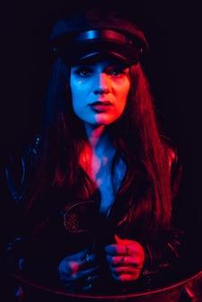 Portrait à la mode d'une jeune fille sexy dans une veste en cuir et une casquette avec un néon