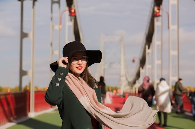 Portrait de mode d'un jeune mannequin heureux avec un maquillage lumineux portant un chapeau noir, des lunettes et une écharpe flottante