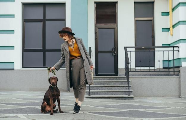 Portrait à la mode de jolie fille avec chien posant