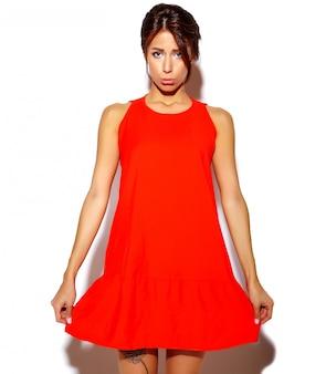 Portrait de mode mignon jeune femme mannequin dans une robe rouge sur un mur blanc