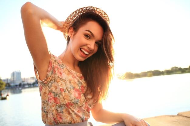 Portrait de mode de mode de vie ensoleillé d'été de jeune femme élégante de hipster. femme aux dents blanches pensant et regardant de côté dans un parc en été