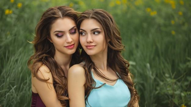 Portrait de mode photo de deux femmes contre l'herbe verte prairie sur la nature